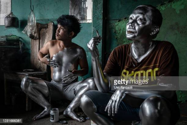 Fernandes , wearing silver paint as prepare for beg on the street on March 10, 2021 in Depok, Indonesia. Fernandes, was a public minivan driver but...
