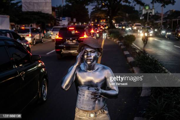 Fernandes , wearing silver paint beg on the street on March 10, 2021 in Depok, Indonesia. Fernandes, was a public minivan driver but due to...