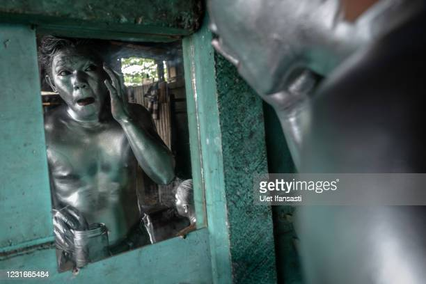 Fernandes , wearing silver paint prepares to beg on the street on March 10, 2021 in Depok, Indonesia. Fernandes, was a public minivan driver but due...