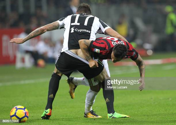 Fernandez Suso of AC Milan tangles with Mario Mandzukic of Juventus FC during the Serie A match between AC Milan and Juventus at Stadio Giuseppe...