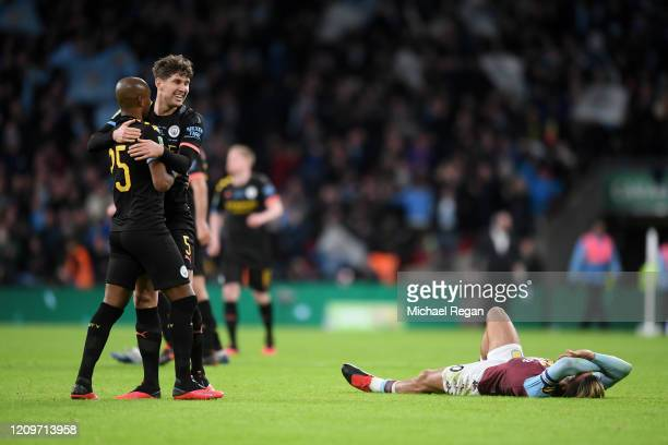 Fernandinho and John Stones of Manchester City celebrate as Jack Grealish of Aston Villa looks dejected following the Carabao Cup Final between Aston...
