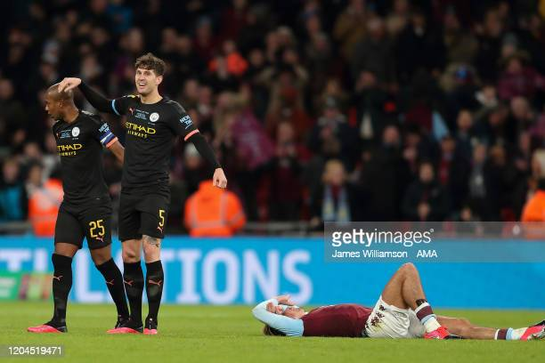 Fernandinho and John Stones of Manchester City celebrate at full time while Jack Grealish of Aston Villa lays on the floor dejected during the...
