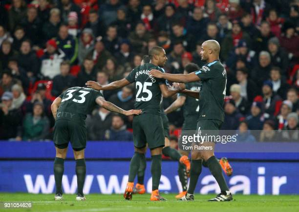 Fernandinho and Vincent Kompany of Manchester City celebrate as David Silva of Manchester City scores their first goal during the Premier League...