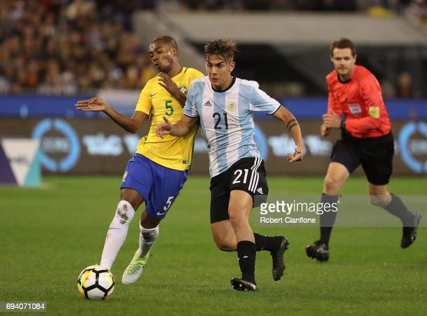 Fernandinho of Brazil and Paulo Dyballa of Argentina compete for the ball during the Brazil Global Tour match between Brazil and Argentina at...