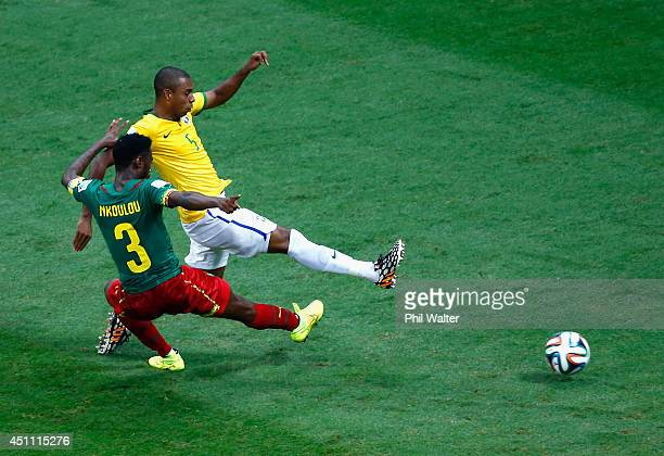 Fernandinho of Brazil scores his team's fourth goal against Nicolas N'Koulou of Cameroon during the 2014 FIFA World Cup Brazil Group A match between...
