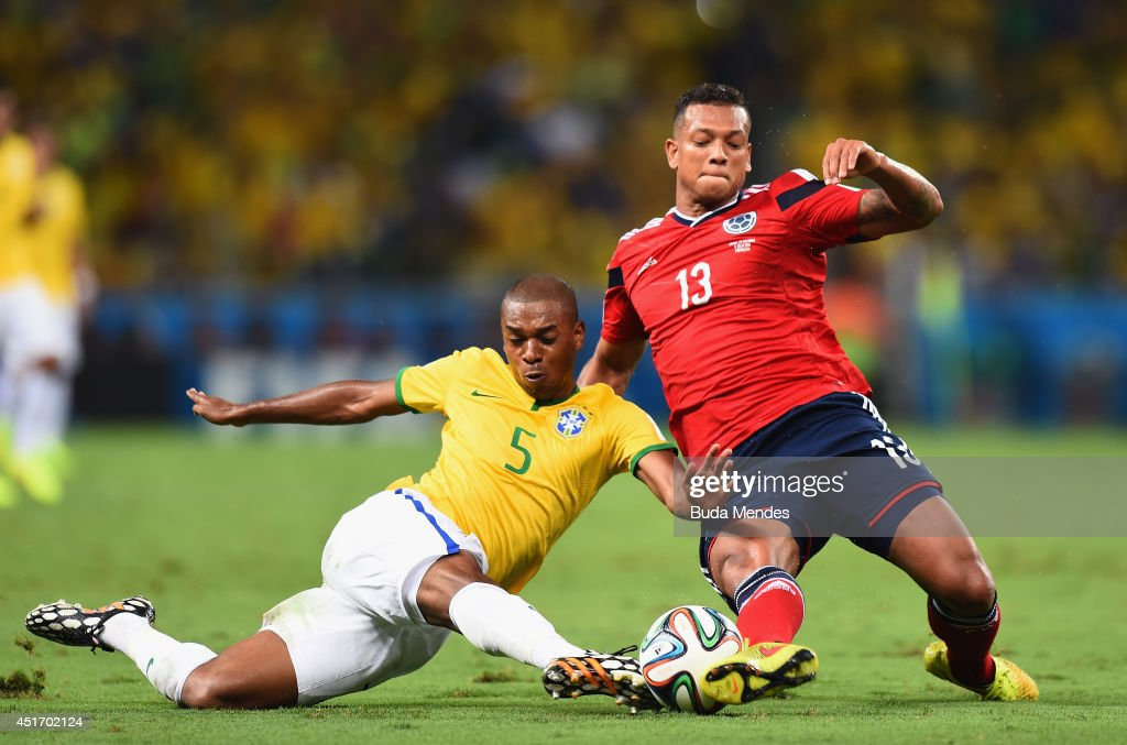 Fernandinho of Brazil tackles Fredy Guarin of Colombia during the 2014 FIFA World Cup Brazil Quarter Final match between Brazil and Colombia at Castelao on July 4, 2014 in Fortaleza, Brazil.