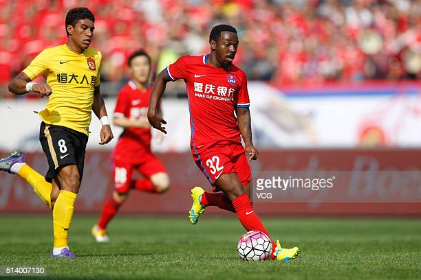 Fernandinho of Chongqing Lifan and Paulinho of Guangzhou Evergrande Taobao vie for the ball during the first round match of CSL Chinese Football...