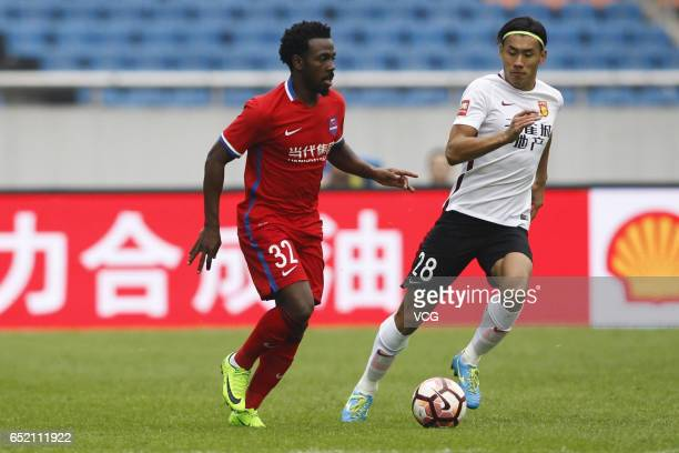 Fernandinho of Chongqing Lifan and Zhang Chengdong of Hebei China Fortune compete for the ball during the 2nd round match of CSL Chinese Football...