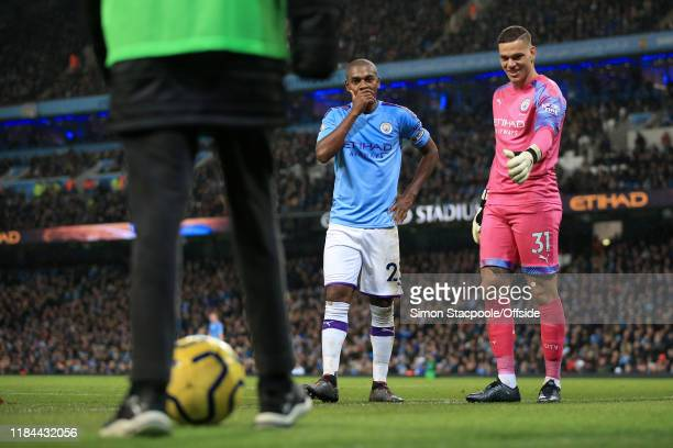 Fernandinho of Man City and Man City goalkeeper Ederson wait to receive the ball from a ballboy during the Premier League match between Manchester...