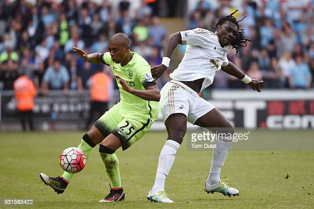 Fernandinho of Manchester City and Bafetimbi Gomis of Swansea City compete for the ball during the Barclays Premier League match between Swansea City...
