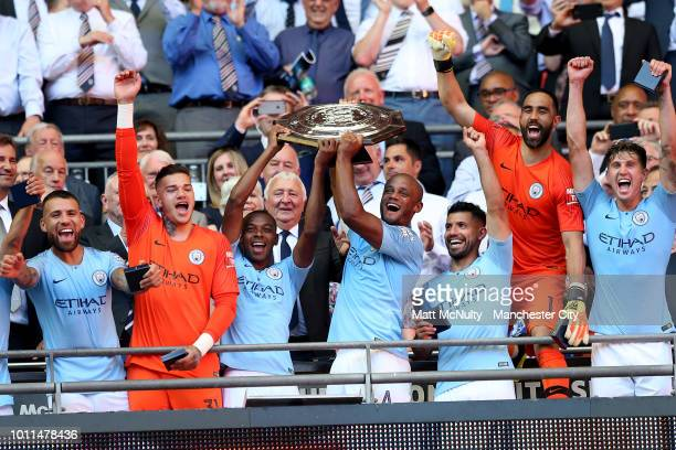 Fernandinho of Manchester City and Vincent Kompany of Manchester City lift the FA Community Shield Trophy following their sides victory in the FA...