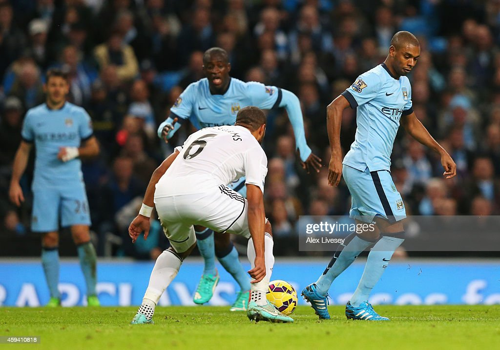 Fernandinho of Manchester City back-heels the ball to Yaya Toure of Manchester City on the way to his goal during the Barclays Premier League match between Manchester City and Swansea City at Etihad Stadium on November 22, 2014 in Manchester, England.