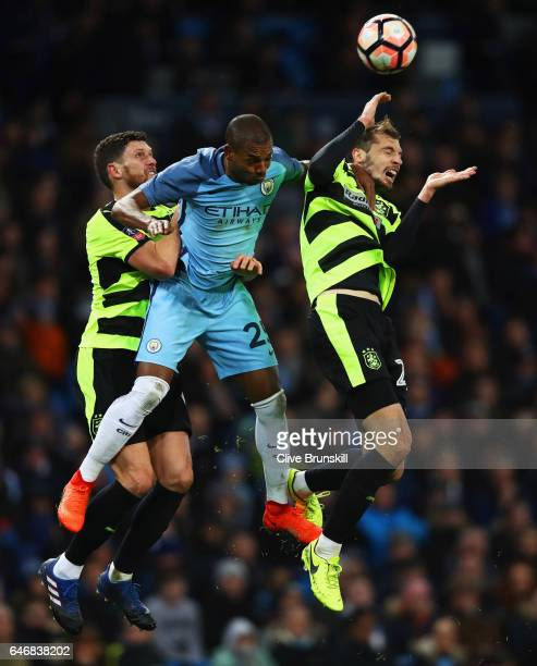 Fernandinho of Manchester City jumps between Mark Hudson and Jon Gorenc Stankovic of Huddersfield Town during The Emirates FA Cup Fifth Round Replay...