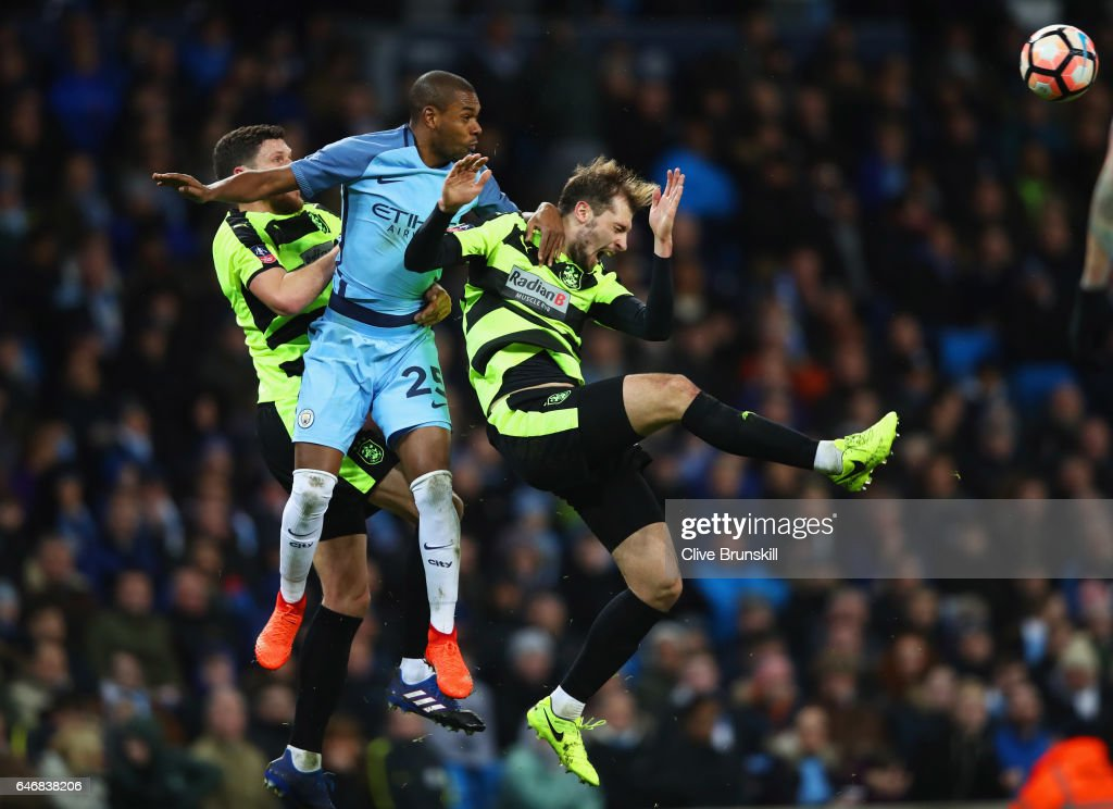 Fernandinho of Manchester City jumps between Mark Hudson (L) and Jon Gorenc Stankovic of Huddersfield Town (R) during The Emirates FA Cup Fifth Round Replay match between Manchester City and Huddersfield Town at Etihad Stadium on March 1, 2017 in Manchester, England.