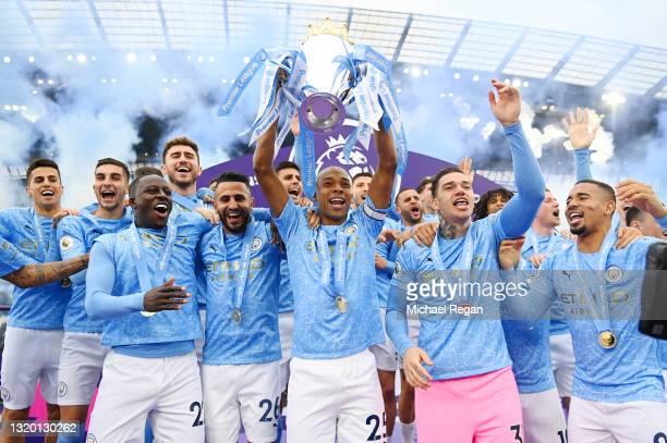 Fernandinho of Manchester City lifts the Premier League Trophy with team mates Benjamin Mendy, Riyad Mahrez, Ederson and Sergio Aguero as Manchester...