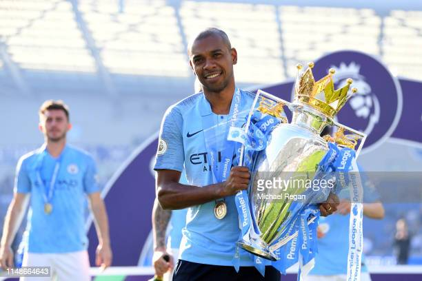 Fernandinho of Manchester City poses with the Premier League Trophy after winning the title during the Premier League match between Brighton & Hove...