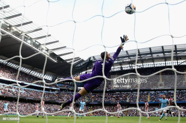 Fernandinho of Manchester City scores his sides fifth goal as Jack Butland of Stoke City attempts to stop it during the Premier League match between...