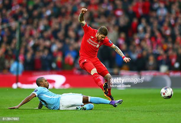 Fernandinho of Manchester City slides to tackle Alberto Moreno of Liverpool during the Capital One Cup Final match between Liverpool and Manchester...