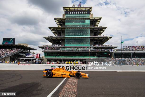 Fernando Alonso driver of the McLarenHondaAndretti Honda drives across the yard of bricks in in front of The Panasonic Pagoda during the running of...