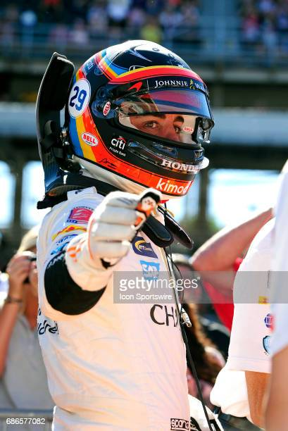 Fernando Alonso driver of the McLarenHondaAndretti Honda reaches out to highfive crew members during qualifying for the Indianapolis 500 on May 21 at...