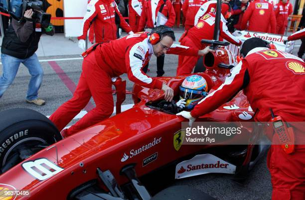 Fernando Alonso of Ferrari and Spain is pushed back in the garage by his mechanics during winter testing at the Ricardo Tormo Circuit on February 3,...