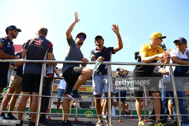 Fernando Alonso of McLaren Honda and Carlos Sainz of Scuderia Toro Rosso greet the crowd on the Drivers Parade during an opening ceremony of 2017...