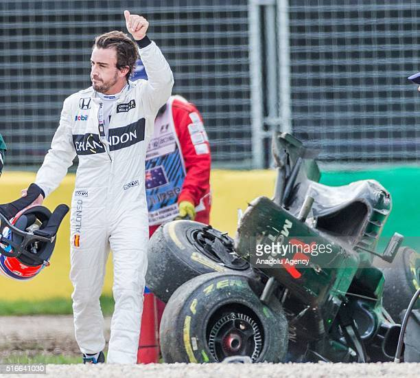Fernando Alonso of McLarenHonda with his helmet off waves to the crowd signalling he is ok as he walks past his destroyed car following a serious...