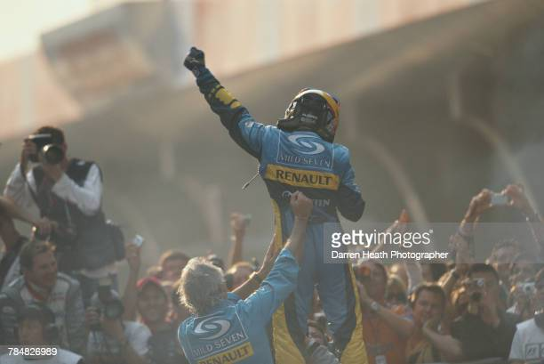 Fernando Alonso of Spain and driver of the Mild Seven Renault F1 Team Renault R25 Renault RS25 V10 is held up by team principal Flavio Briatore as...