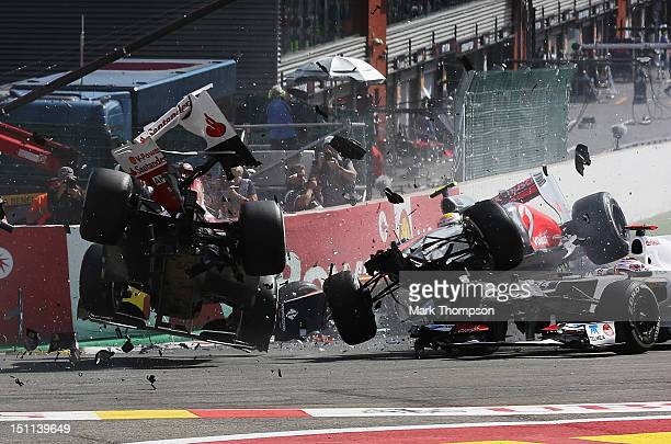 Fernando Alonso of Spain and Ferrari and Lewis Hamilton of Great Britain and McLaren collide and crash out at the first corner at the start of the...