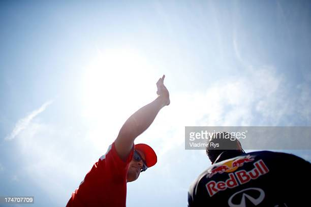 Fernando Alonso of Spain and Ferrari and Mark Webber of Australia and Infiniti Red Bull Racing are seen prior to the Hungarian Formula One Grand Prix...