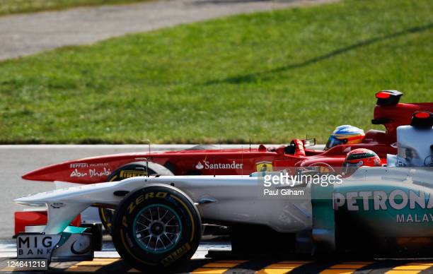 Fernando Alonso of Spain and Ferrari and Michael Schumacher of Germany and Mercedes GP fight for position at the first chicane during the Italian...