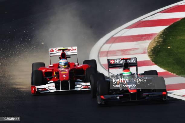 Fernando Alonso of Spain and Ferrari and Sakon Yamamoto of Japan and Hispania Racing Team drive thru the final corner during practice for the Korean...