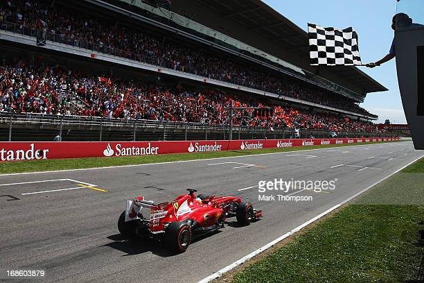 Fernando Alonso of Spain and Ferrari celebrates as he crosses the finishing line to win the Spanish Formula One Grand Prix at the Circuit de...