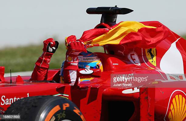 Fernando Alonso of Spain and Ferrari celebrates as he drives into parc ferme after winning the Spanish Formula One Grand Prix at the Circuit de...