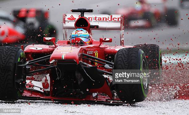 Fernando Alonso of Spain and Ferrari crashes into the gravel trap at turn one after sustaining front wing damage during the Malaysian Formula One...