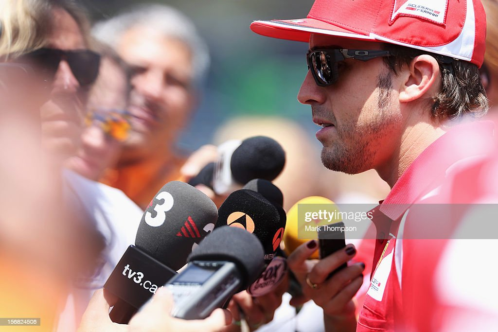 Fernando Alonso of Spain and Ferrari is interviewed by the media in the paddock during previews for the Brazilian Formula One Grand Prix at the Autodromo Jose Carlos Pace on November 22, 2012 in Sao Paulo, Brazil.