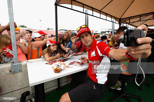 Fernando Alonso of Spain and Ferrari meets fans at the drivers autograph session during previews to the Hungarian Formula One Grand Prix at the...