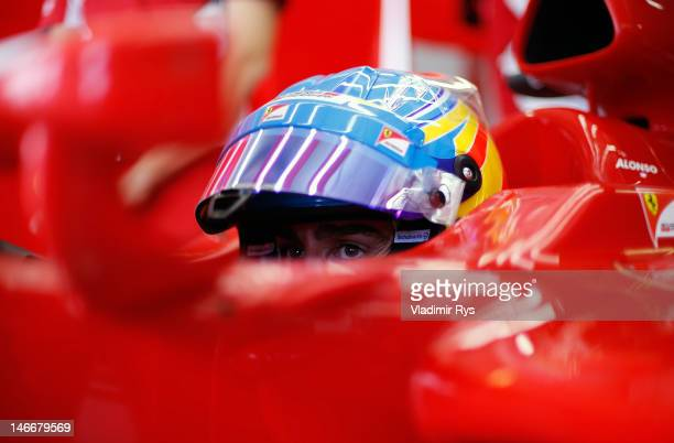 Fernando Alonso of Spain and Ferrari sits in his car in the garage during practice for the European Grand Prix at the Valencia Street Circuit on June...