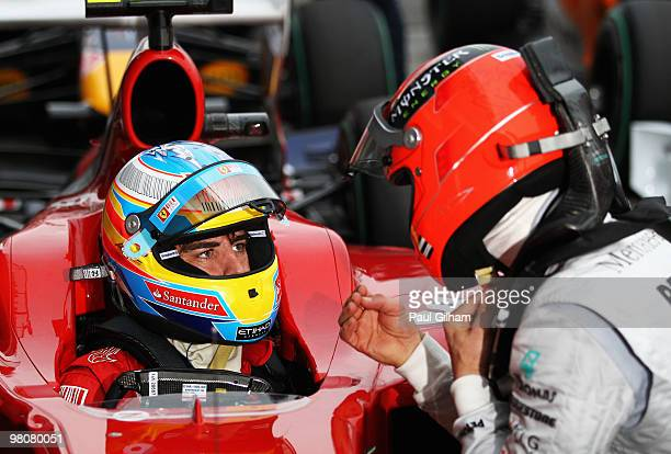 Fernando Alonso of Spain and Ferrari talks with Michael Schumacher of Germany and Mercedes GP in parc ferme after qualifying for the Australian...