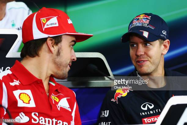 Fernando Alonso of Spain and Ferrari talks with Sebastian Vettel of Germany and Red Bull Racing at the drivers press conference during previews for...