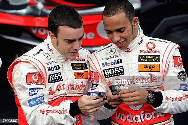 Fernando Alonso of Spain and Lewis Hamilton of Great Britain use their mobile phones during The Vodafone McLaren Mercedes Formula One Grand Prix team...