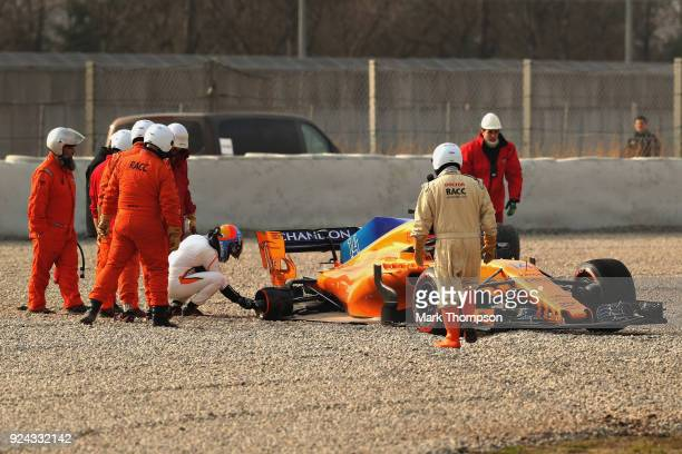 Fernando Alonso of Spain and McLaren F1 checks over his car after stopping on track during day one of F1 Winter Testing at Circuit de Catalunya on...
