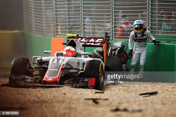 Fernando Alonso of Spain and McLaren Honda climbs out of his car after crashing Esteban Gutierrez of Mexico, Haas F1 Team Haas-Ferrari VF-16 Ferrari...