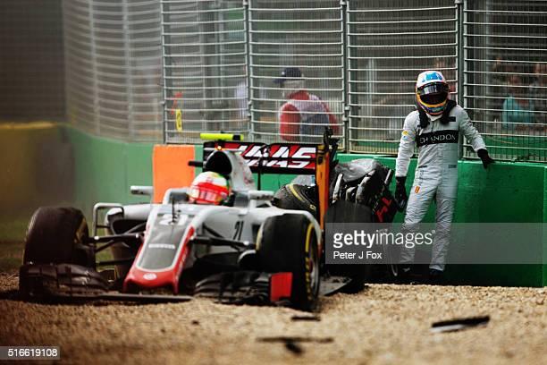 Fernando Alonso of Spain and McLaren Honda climbs out of his car after crashing Esteban Gutierrez of Mexico Haas F1 Team HaasFerrari VF16 Ferrari...