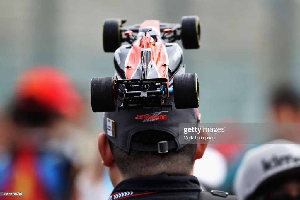 A Fernando Alonso of Spain and McLaren Honda fan wears a hat decorated with a model car during previews ahead of the Formula One Grand Prix of Japan at Suzuka Circuit on October 5, 2017 in Suzuka.