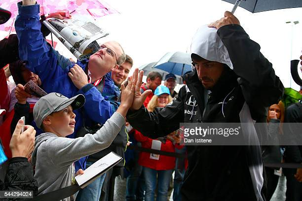 Fernando Alonso of Spain and McLaren Honda highfives a young fans as he arrives for the Formula One Grand Prix of Austria at Red Bull Ring on July 3...