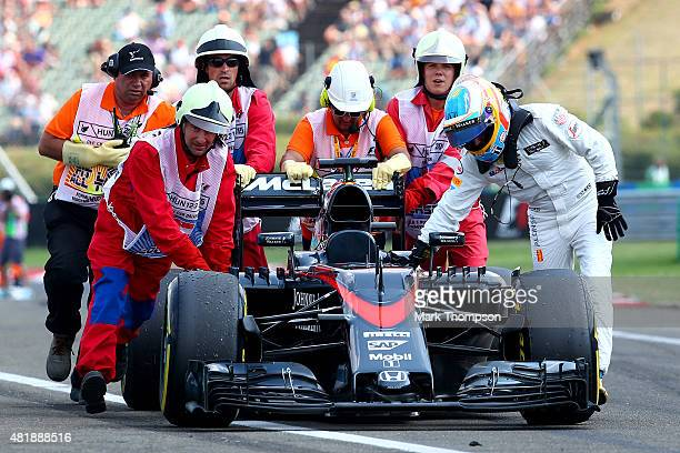 Fernando Alonso of Spain and McLaren Honda pushes his car back to the pit lane with the assistance of the marshalls during qualifying for the Formula...