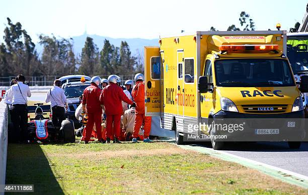 Fernando Alonso of Spain and McLaren Honda receives medical assistance after crashing during day four of Formula One Winter Testing at Circuit de...