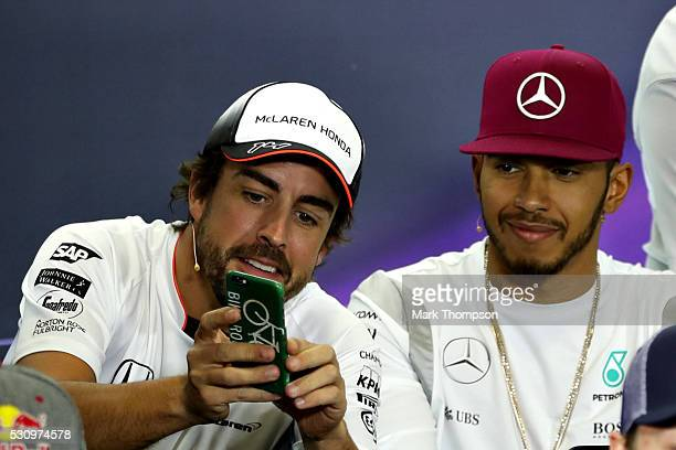 Fernando Alonso of Spain and McLaren Honda shows Lewis Hamilton of Great Britain and Mercedes GP his phone in the Drivers Press Conference during...