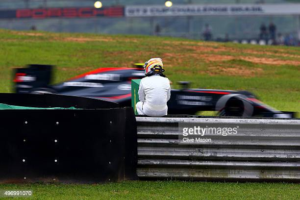 Fernando Alonso of Spain and McLaren Honda sits on a fance at the side of the track as his teammate Jenson Button of Great Britain and McLaren Honda...